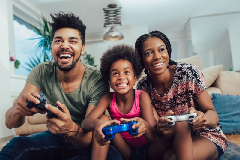 A man, a woman, and a young girl playing video games together